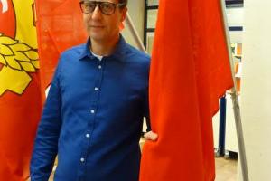 """Anton Monti esitelmöi 30.3. 2016 Porin pääkirjastossa. Sen tiloissa oli samaan aikaan Porin Sosiaalidemokraattisen Kunnallisjärjestön valokuvanäyttely """"Eetun hengessä 110 vuotta"""" lippurekvisiittoineen. Monti otti lähituntumaa näyttelyyn."""